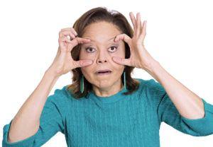 Vrouw die haar hangende oogleden probeert open te doen